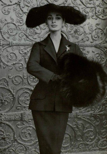 Christian Dior suit with a fox fur muff and wide brimmed hat.
