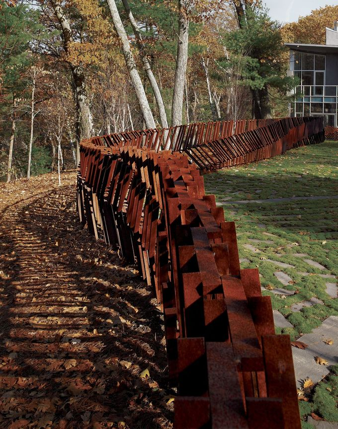This Cor-Ten steel fence, which the landscape architect and artist Mikyoung Kim designed for Bob Davoli and Eileen McDonagh, winds its way through the woods of Lincoln, Massachusetts, like a serpent skeleton fished out of the adjacent Farrar Pond. Unlike most fences—which follow rigid property lines in the utilitarian service of exclusion or containment—it meanders like a weathered Andy Goldsworthy sculpture that just happens to keep the family dogs near home as well. Photo by Charles Mayer.