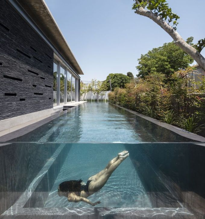 Swimming pool features entirely glass sides and sits above ground, making swimmers look as though they might be floating tranquilly in thin air