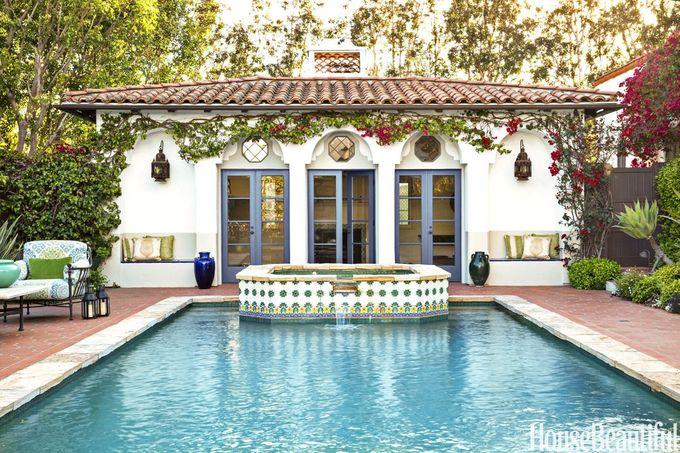 凸起的按摩浴缸上的瓷砖在泳池尽头创造了一个焦点。法式门可通往泳池屋。