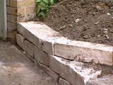 DIYNetwork.com网站的专家向您展示了如何建造一个不含灰浆的挡土墙,以防止倾斜场地的灰尘进入车道。