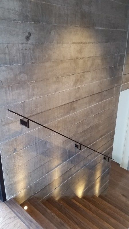 Amazing feature stairs. Dramatic light effect and shadowing on off shutter timber grain precast concrete wall, sleek flat cast iron handrail.