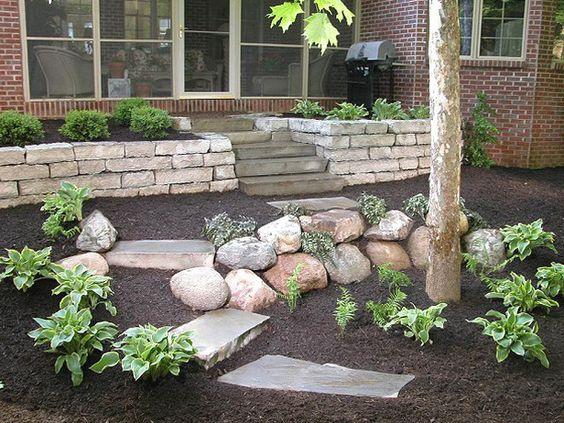 根据DIYNetwork.com专家的指示,在顶部建造一个天然石材挡土墙和楼梯,上面设有石板露台。