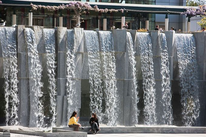 Women enjoy a sunny afternoon in front of the Yerba Buena Gardens waterfall in downtown San Francisco, California
