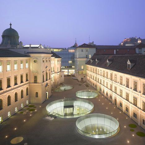 Cavernous holes in the courtyard of three museum buildings in Graz, Austria, lead underground into a new, shared entrance by Spanish architects Nieto Sobejanoand local firmeep architekten.