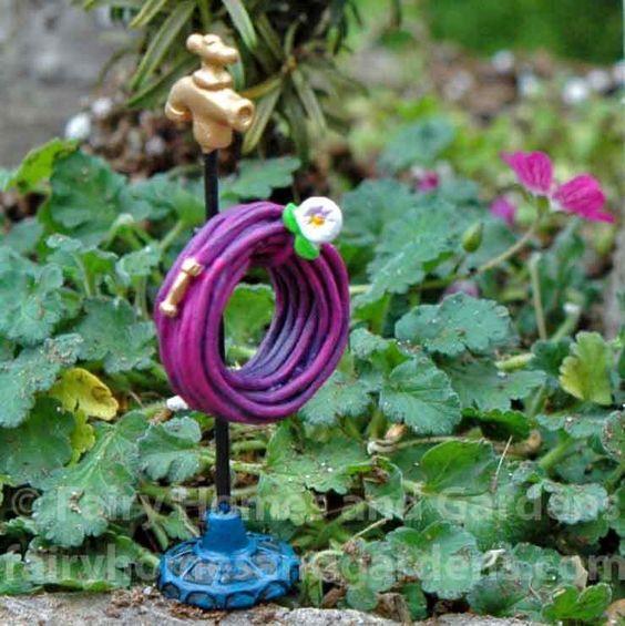 在微型支架上盘绕的微小紫色花园软管是您的微型童话花园的完美配件。