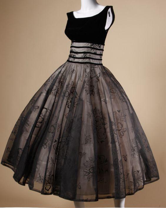 """别致1950年代的黑色天鹅绒和黑色倦怠纯粹透明硬纱派对礼服,带有巨大的扫掠,并内置于衬里。货架胸围和1950年代的经典款式。倦怠花卉设计具有多色金属闪光斑点。后部金属拉链开合。这件连衣裙应该适合现代的XS-S。尺寸:胸围:28""""腰围:26""""臀围:42""""总长:47"""""""