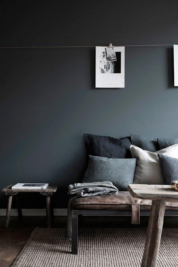 有枕头的灰色沙发反对木炭墙壁。