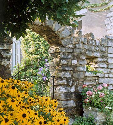 在院子里加一块石墙,创造一个持久而优雅的外壳。
