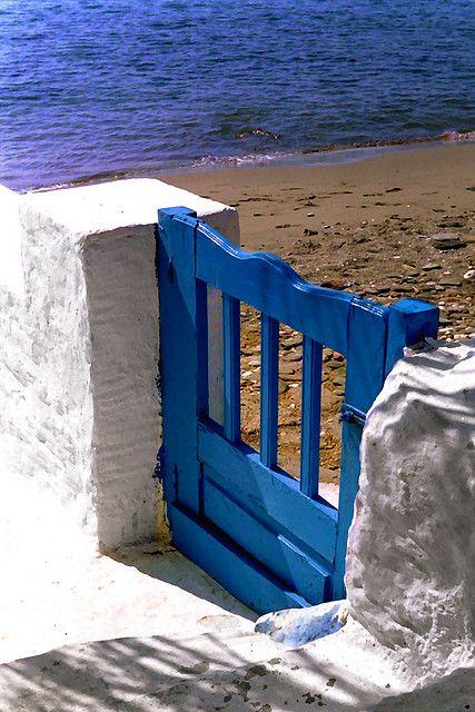 俯视一个空的海滩的微小的蓝色木门。伊斯特拉海滩。蒂诺斯岛,基克拉迪群岛。希腊。