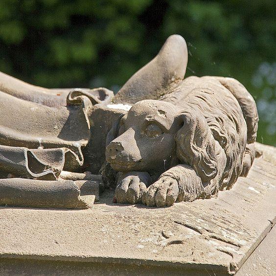 即使在死亡中,这条忠实的狗仍然蜷缩在他主人的脚下。在德国法兰克福的主要墓地(Hauptfriedhof)看到。