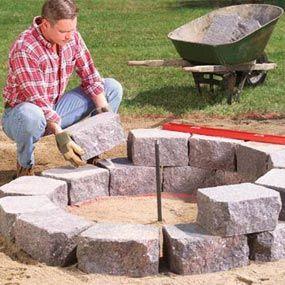建造这个简单,有吸引力的石火坑环,挡土墙石板环绕着石板,是家庭聚会的理想场所。