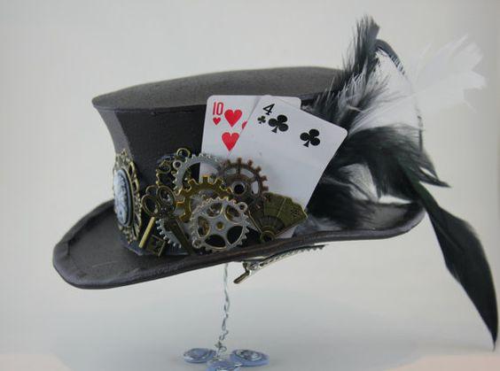 深褐色迷你礼帽,饰以维多利亚时代的浮雕,金属钥匙,剪刀和风扇饰物,以及蒸汽朋克手表。帽子还配有微型扑克牌和装饰羽毛。手工制作的彩绘工艺泡沫,这顶帽子...