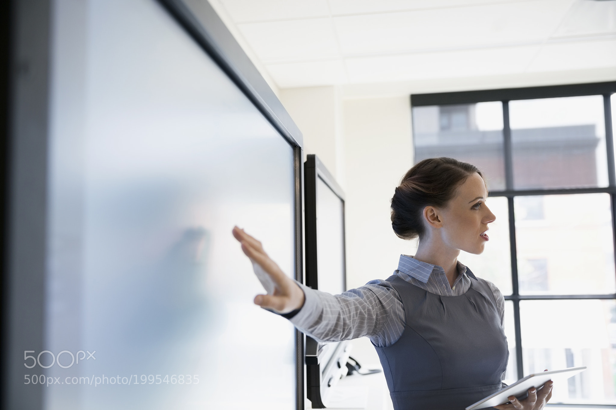Businesswoman with digital tablet leading meeting at television in conference room