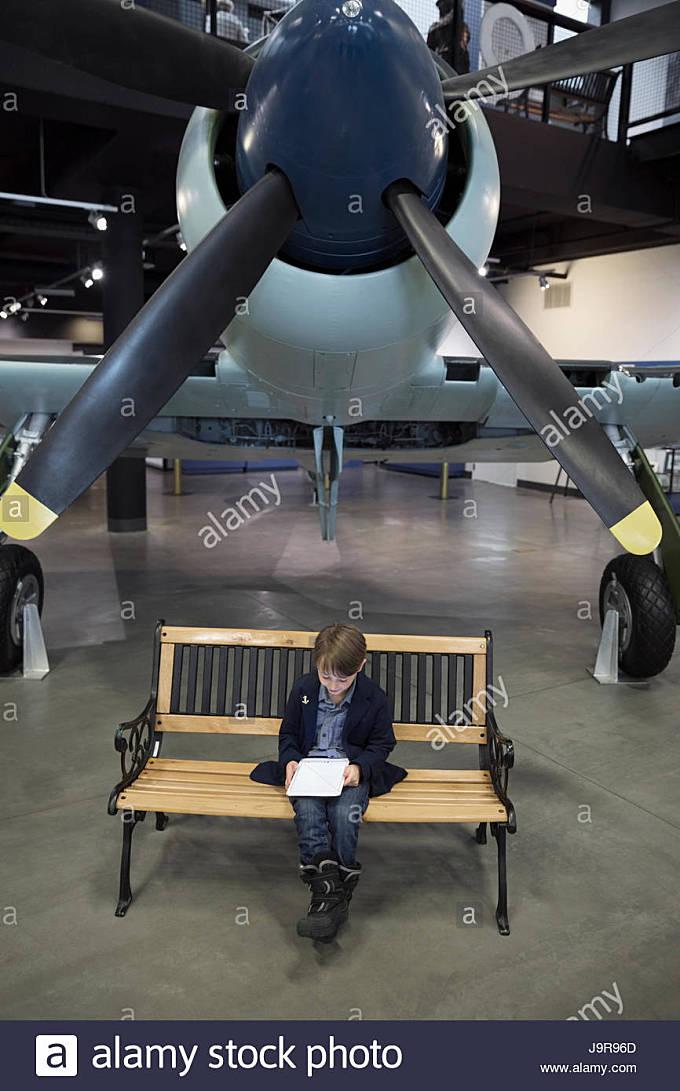 Boy using digital tablet on bench below propellor airplane in war museum hangar - Stock Image