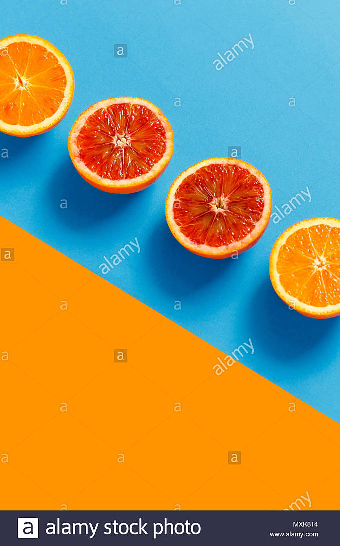 Oranges cut in half on a orange and blue background. Complementary colors - Stock Image