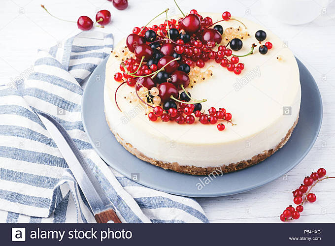 New York cheese cake with berries on white wooden table. Angle view. - Stock Image