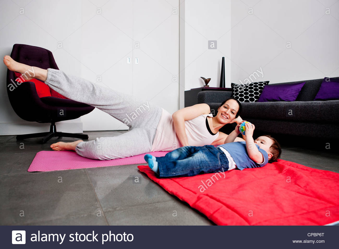 A mother and her baby son exercising at home - Stock Image