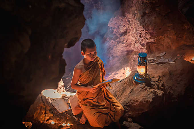 Neophyte reading religion in a cave