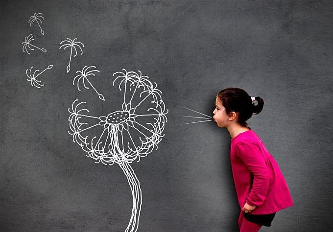 Little cute girl blowing dandelion seeds on chalkboard