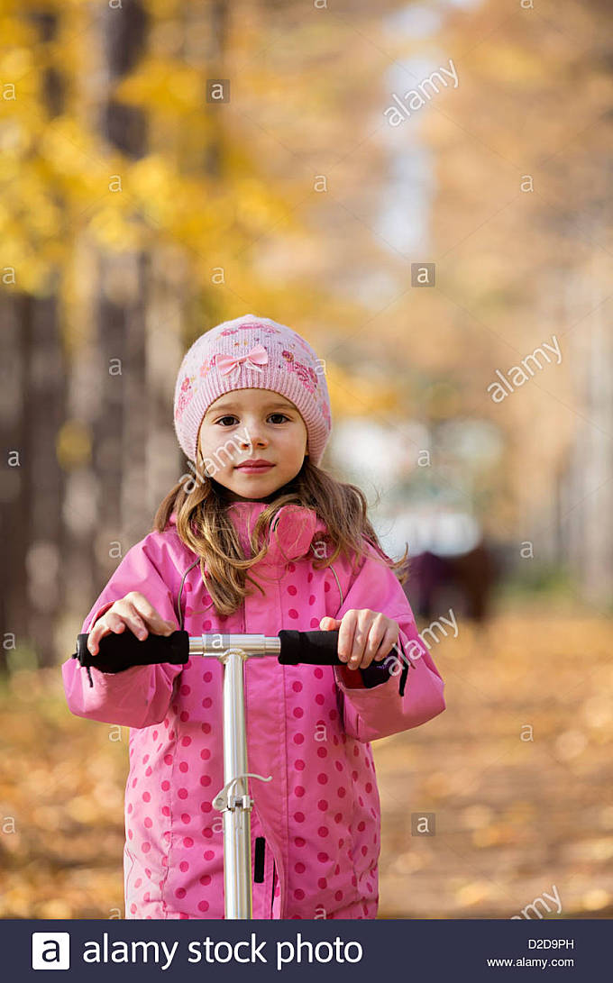 A young girl standing on a push scooter - Stock Image