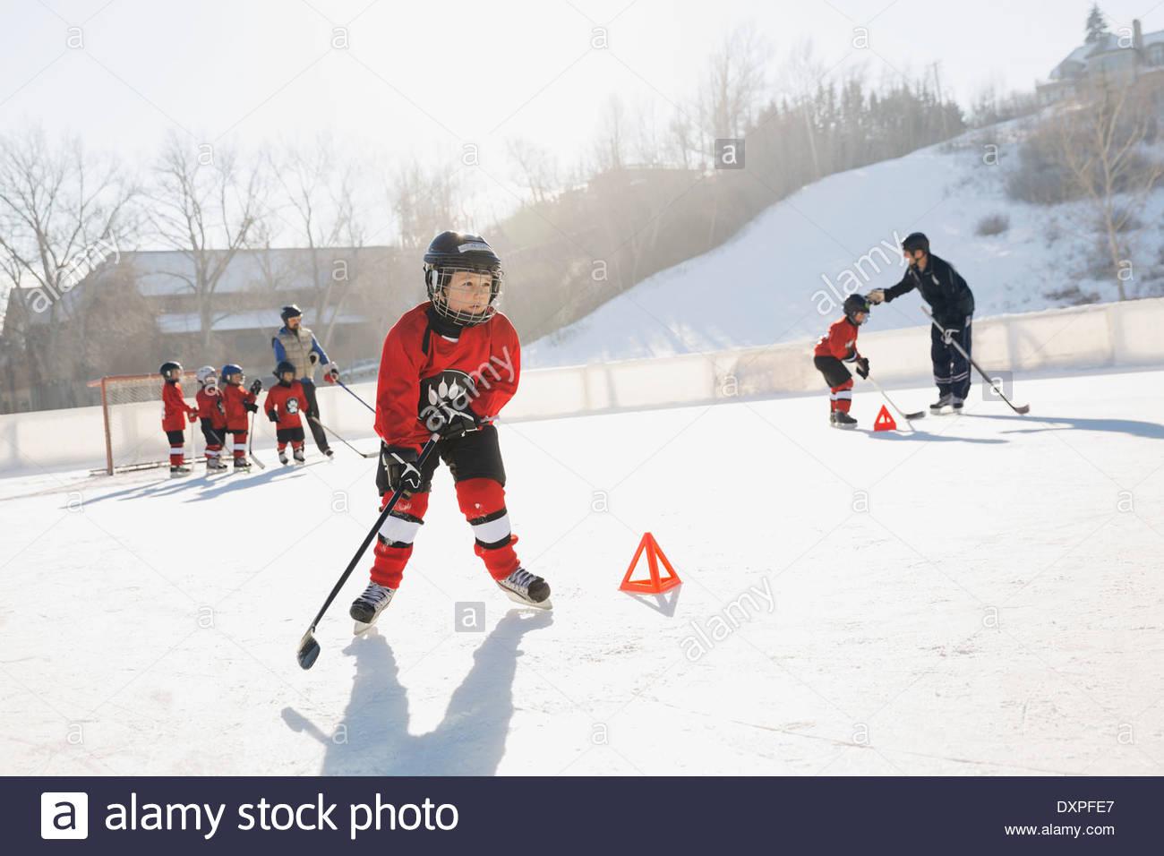 Ice hockey players training on outdoor skating rink - Stock Image