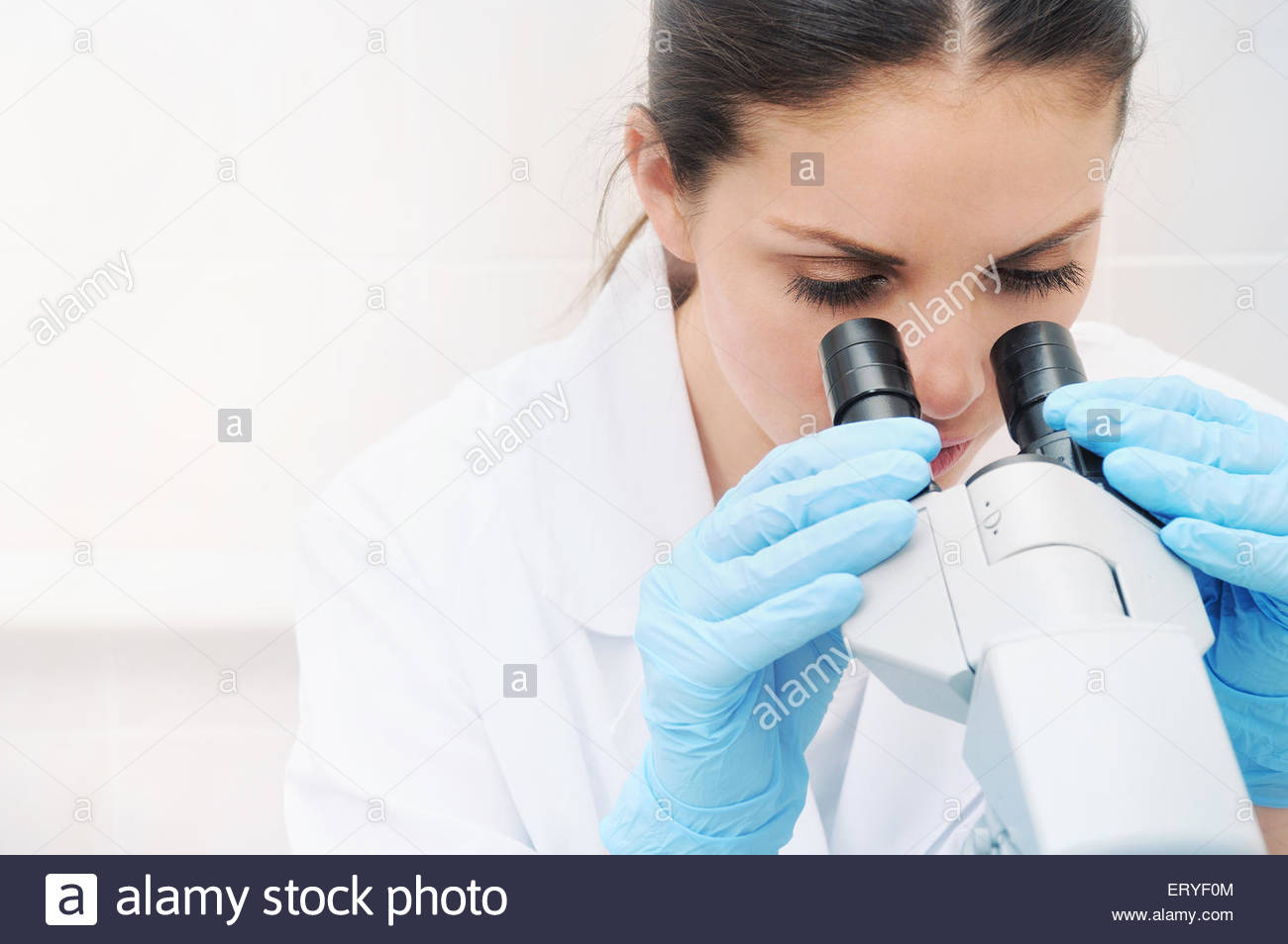 young woman medical researcher looking through microscope in laboratory, medicine concept - Stock Image