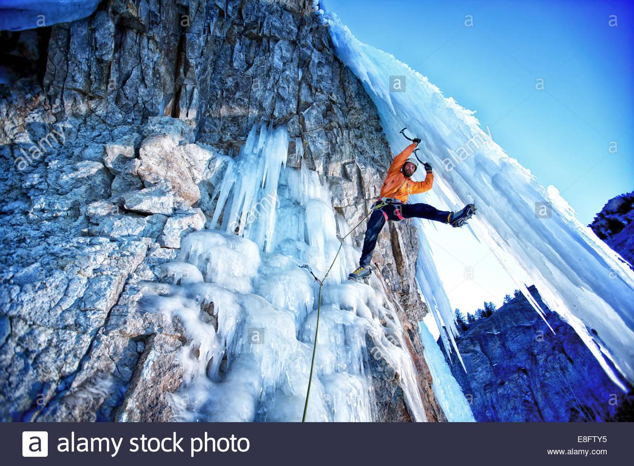 Ice climber climbing onto ice shaft, Lake City, Colorado, America, USA - Stock Image