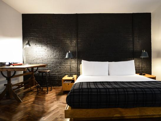 Who wouldn't want to stay in this rustic style hotel room? The main feature in this bedroom at the Ace Hotel is an exposed black brick wall. A platform bed made with white and black linens anchors the room and side tables with black table lamps act as bedside tables. The room's hardwood is laid in a zig-zag pattern, Chevron-like pattern and an antique table and stool act as a work station.