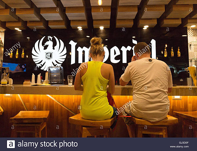 A young couple sitting at a bar having a drink, rear view, San Jose airport ,Costa Rica - Stock Image