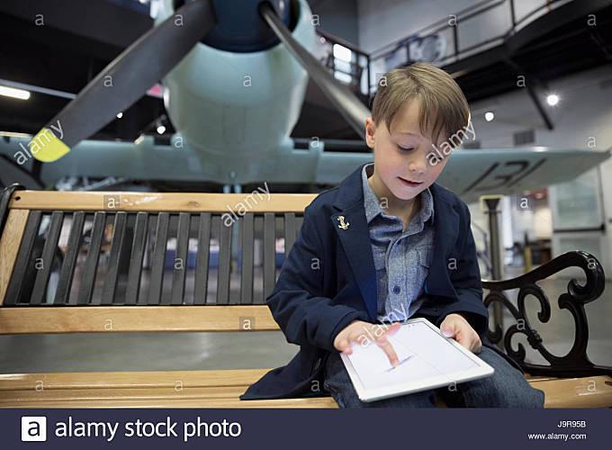 Boy drawing on digital tablet on bench below propellor airplane in war museum hangar - Stock Image