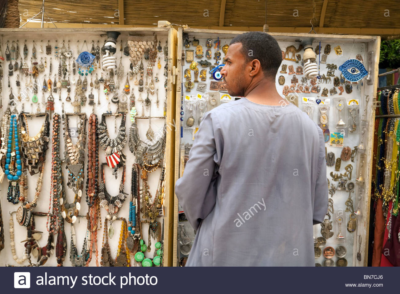 A jewellery stall and stallkeeper, Kom Ombo, Upper Egypt - Stock Image