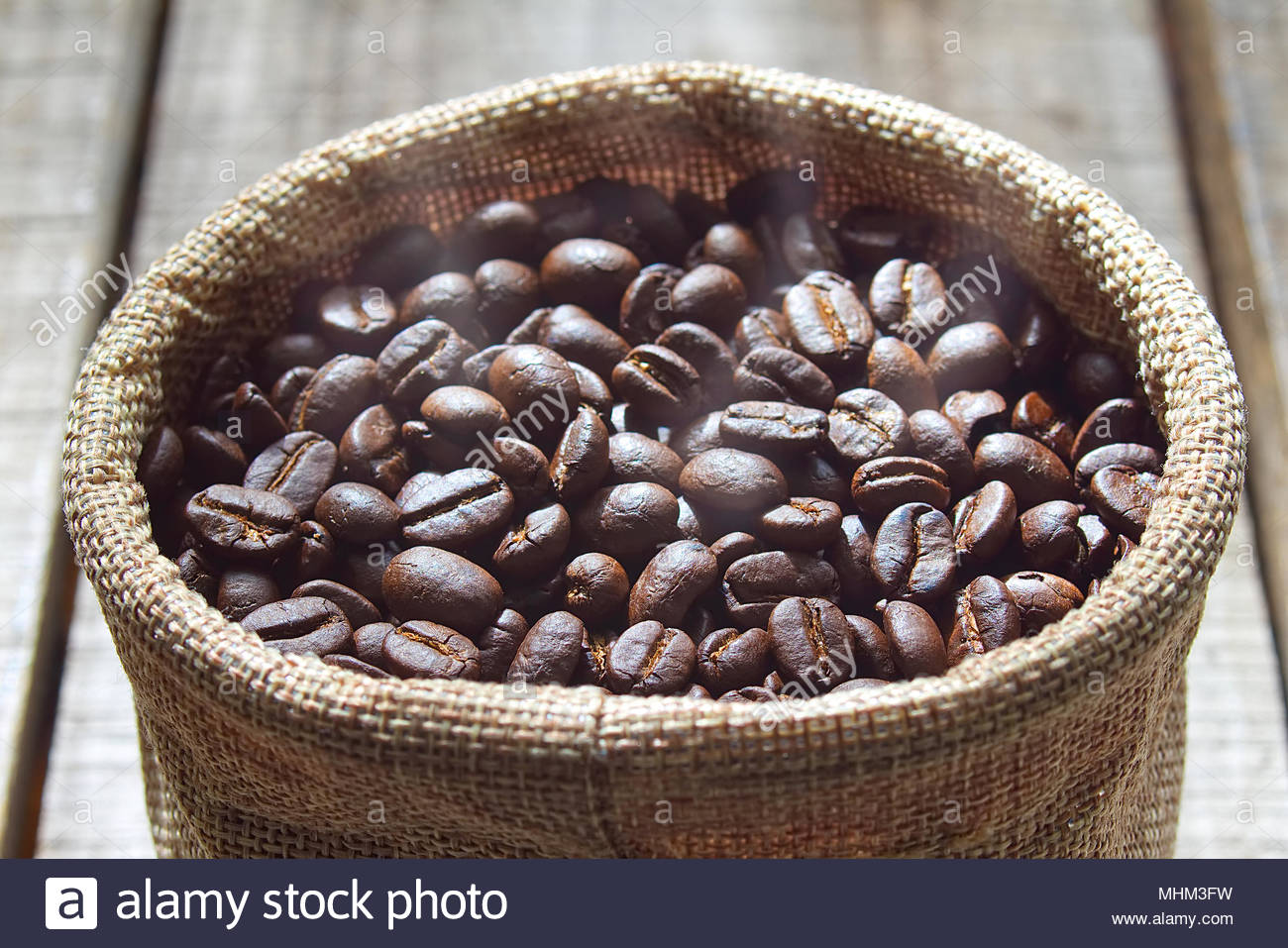 Close up fresh coffee beans keep in bag after blending on wood table. - Stock Image