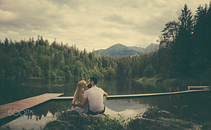 Young couple kissing in front beautiful lake landscape