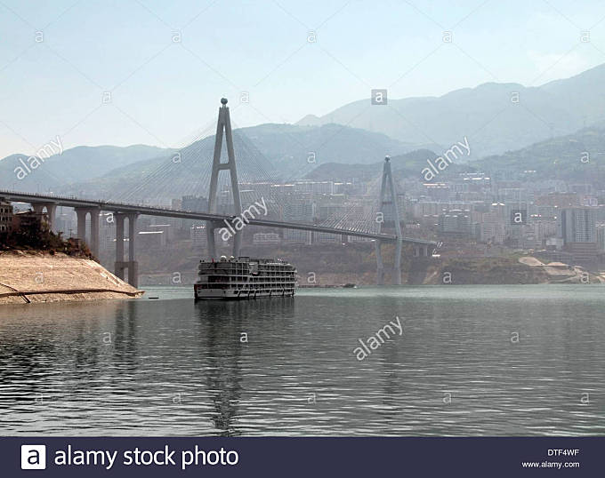 foggy scenery along the Yangtze River in China including bridge and tourist boat - Stock Image