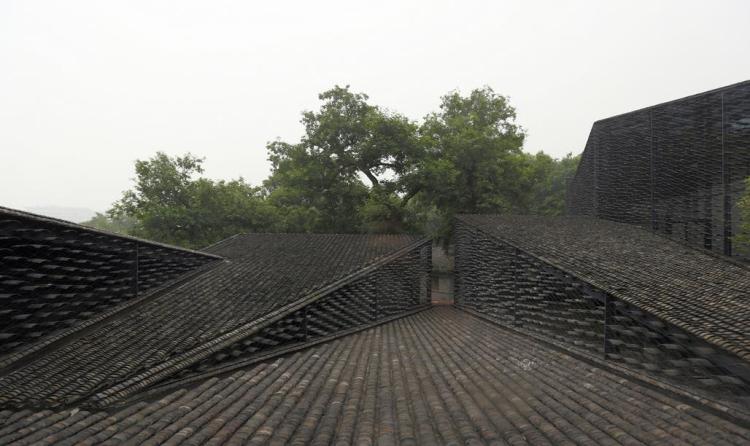 """中国美院民艺博物馆位于杭州郊区,被优美的茶园所环绕。隈研吾通过设计出高低错落的展示空间,试图探索人与艺术,人与自然的全新关系。建筑设计没有抹去原有场地特点,而是遵循山势变化进行创作。""""瓦""""是这座建筑最为显著的设计元素。这些瓦片全都取自当地农家,被灵活地运用于建筑屋顶,建筑中庭地面及建筑立面。除了瓦,建筑还用到了当地原生建筑材料,如木材。瓦在建筑屋顶的使用,很好地回应了周围场所环境,营造出了小型村落的意境。建筑玻璃幕墙之外的丝网结构将一片片瓦如鳞片一样悬挂在半空,在彰显地域历史特点的同时,营造出轻盈而通透的"""