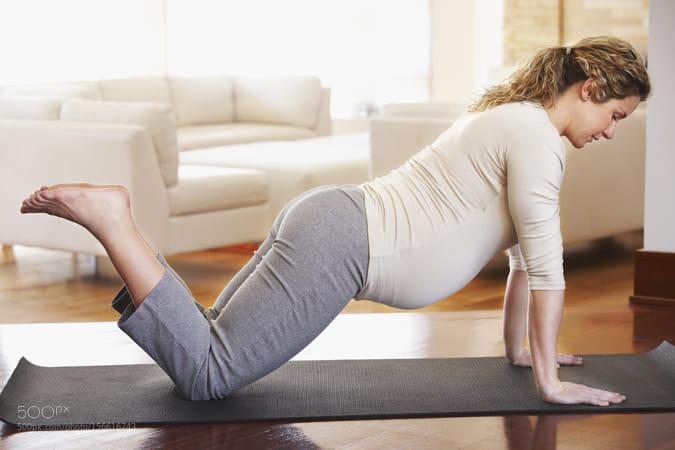 Pregnant Caucasian woman practicing yoga