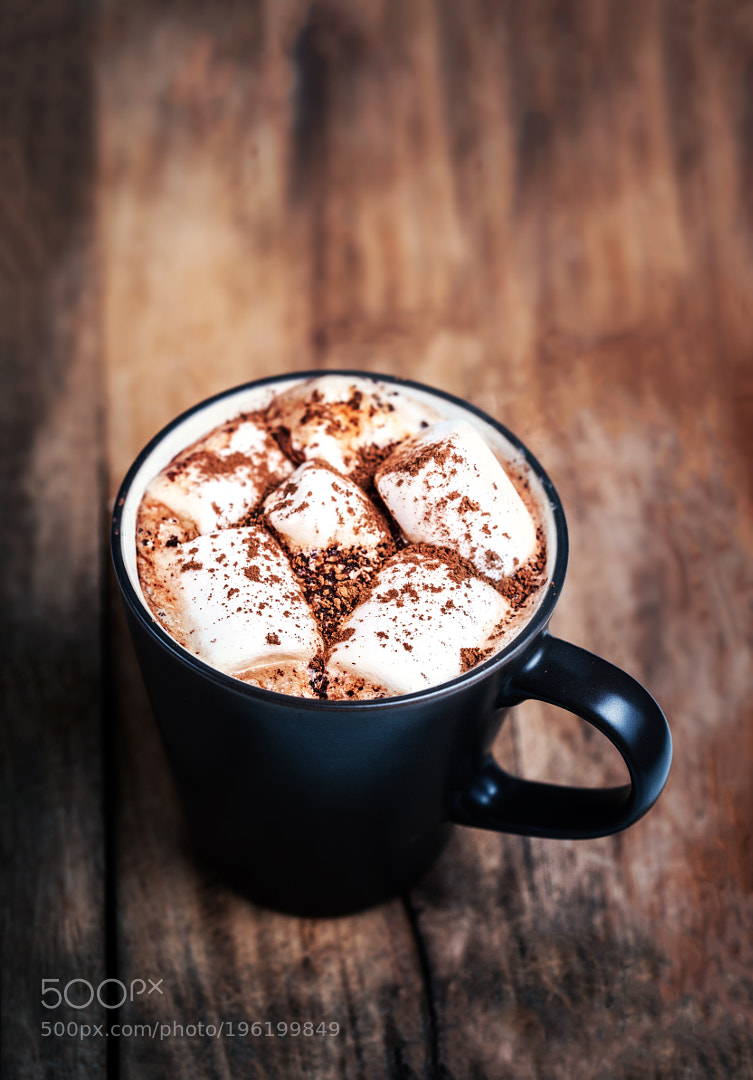 Hot chocolate with marshmallows on vintage wooden table close up