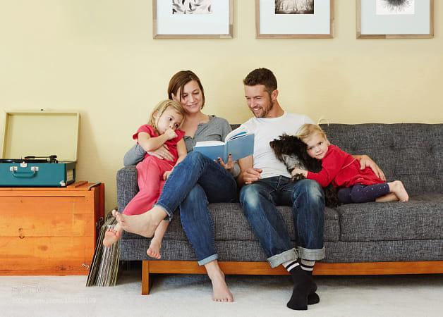 Caucasian family reading on sofa