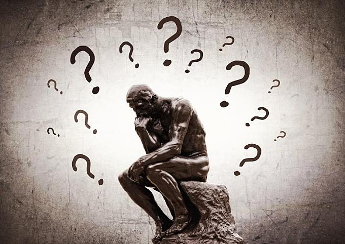 Rodins Thinker surrounded by question marks