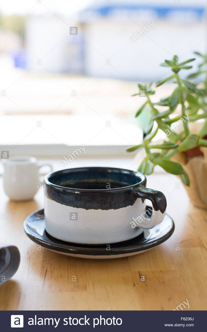 Hand-crafted mug with coffee in a restaurant environment. - Stock Image