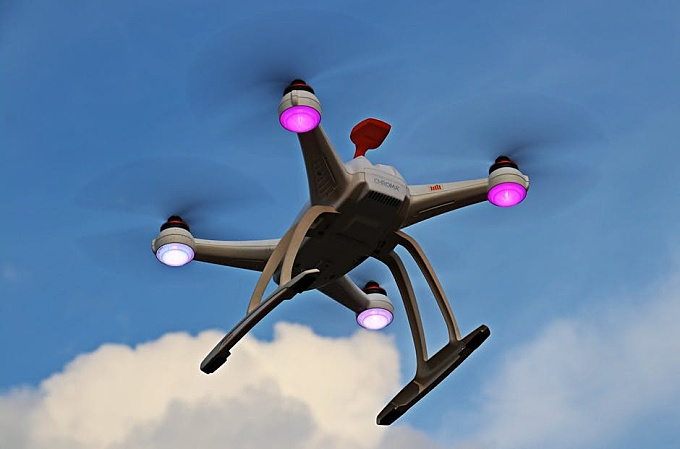 Turned-on White Quadcopter in the Sky