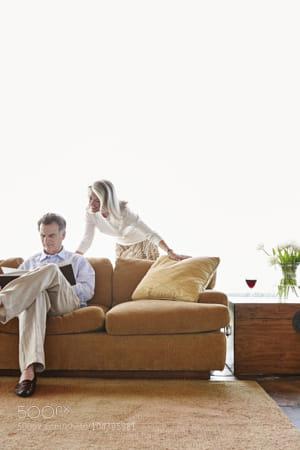 Older Caucasian couple reading book on sofa