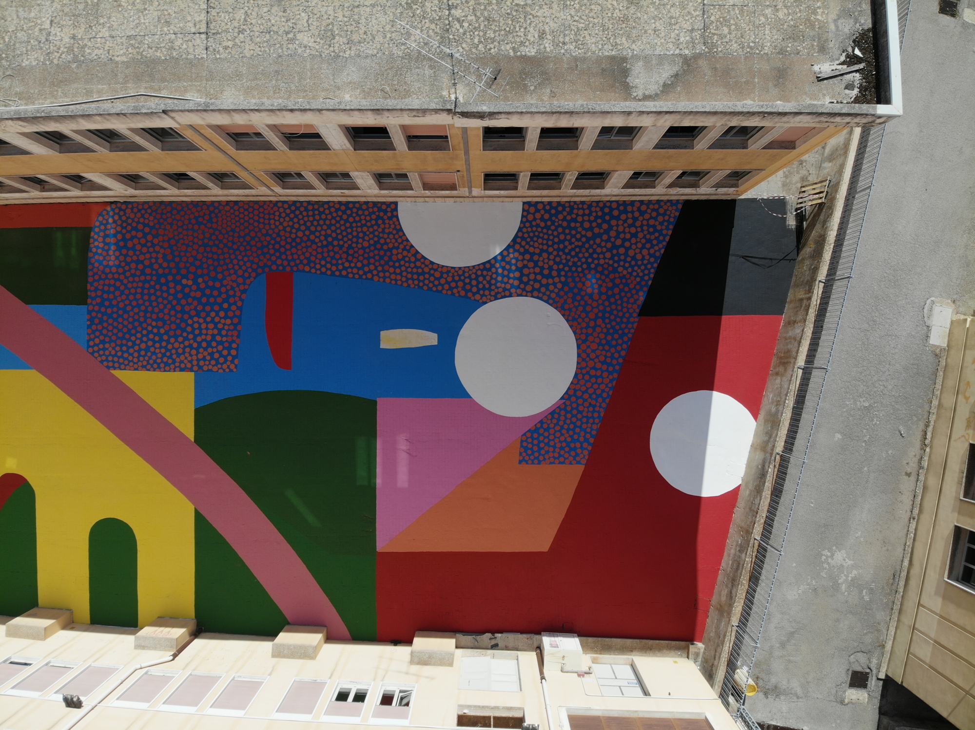 A Mural of Brightly Colored Shapes and Clusters of Spots Gives a Striking Update to a School Courtyard in Sicily
