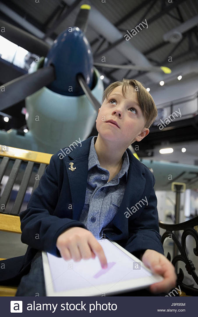Curious boy drawing on digital tablet below propellor airplane in war museum hangar - Stock Image