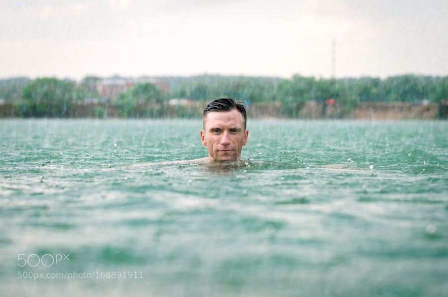 Man swimming in lake under the rain in thunderstorm