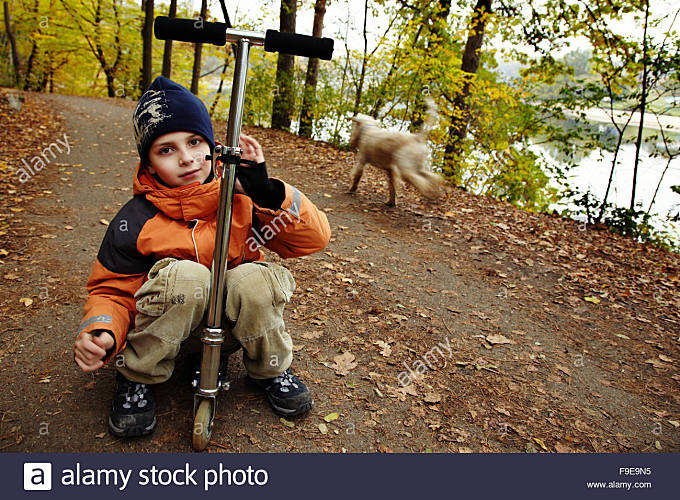 Small Boy sitting on Scooter - Stock Image