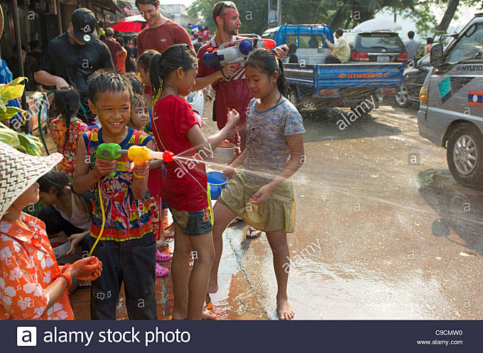 Young Lao boy with super-soaker taking part in water fight, Lao New Year (Pi Mai Lao), Luang Prabang, Laos - Stock Image