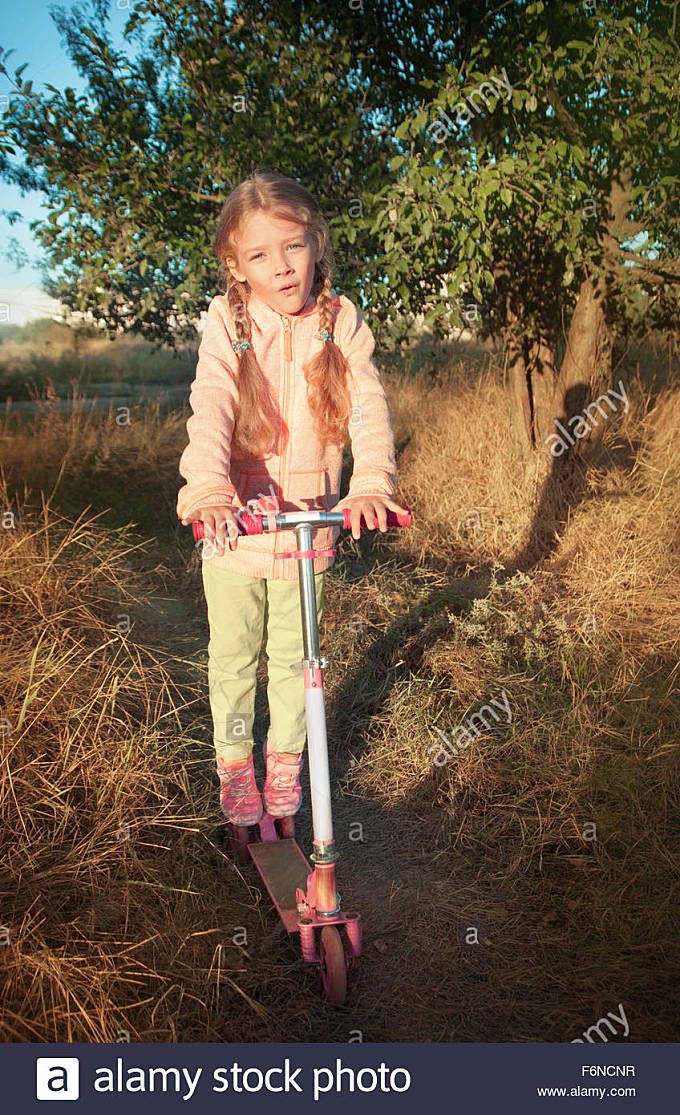 Beautiful girl driving scooter on rural road outdoor in nature - Stock Image
