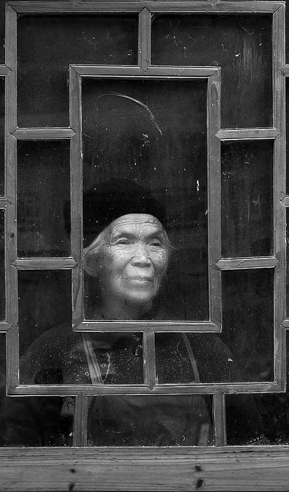 Old woman, dirty window, cold day